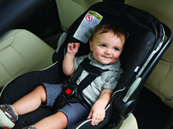 A toddler is buckled into a rear-facing child safety seat.